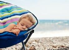 Behandla som ett barn pojken som sovar på stranden Royaltyfri Foto