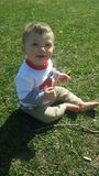 Behandla som ett barn pojken som spelar i sommargräs royaltyfri fotografi
