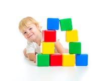 Behandla som ett barn pojken som spelar med byggnadskvarter Arkivfoto