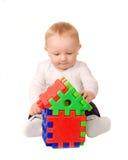 Behandla som ett barn pojken som spelar med byggnadspusslet Royaltyfri Foto