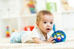 Behandla som ett barn pojken som spelar med den inomhus leksaken Royaltyfri Bild