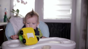 Behandla som ett barn pojken som spelar med en leksakbil som sitter i en behandla som ett barnstol behandla som ett barn det gamm stock video