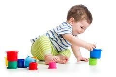 Behandla som ett barn pojken som spelar med färgkoppleksaker Royaltyfria Bilder