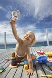 Behandla som ett barn pojken som spelar med leksaker på farstubron royaltyfria foton