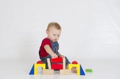 Behandla som ett barn pojken som spelar med ljust färgade träkvarter Arkivbilder