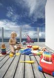 Behandla som ett barn pojken som spelar med massor av leksaker på farstubron Arkivfoto