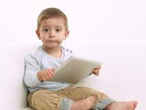 Behandla som ett barn pojken som spelar med minnestavlan Arkivbilder