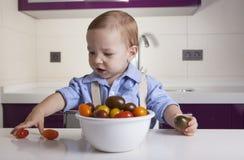 Behandla som ett barn pojken som spelar med mogna färgrika körsbärsröda tomater Arkivfoton