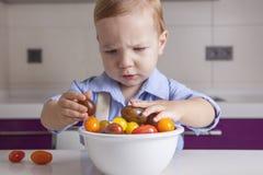 Behandla som ett barn pojken som spelar med mogna färgrika körsbärsröda tomater Fotografering för Bildbyråer