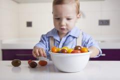 Behandla som ett barn pojken som spelar med mogna färgrika körsbärsröda tomater Royaltyfri Fotografi