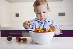 Behandla som ett barn pojken som spelar med mogna färgrika körsbärsröda tomater Arkivbilder
