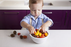 Behandla som ett barn pojken som spelar med mogna färgrika körsbärsröda tomater Arkivfoto