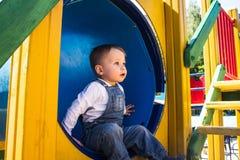Behandla som ett barn pojken som spelar på lekplatsen fotografering för bildbyråer