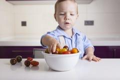 Behandla som ett barn pojken som tar mogna färgrika körsbärsröda tomater Royaltyfri Foto