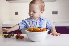 Behandla som ett barn pojken som tar mogna färgrika körsbärsröda tomater Arkivbilder