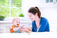 Behandla som ett barn pojken som äter hans första fasta mat Arkivbild
