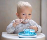 Behandla som ett barn pojken som äter yoghurt Fotografering för Bildbyråer