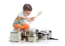 Behandla som ett barn pojken som trummar att spela med krukor arkivbilder