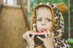 Behandla som ett barn pojken som spelar i trädgården Pojken som äter vattenmelon Royaltyfri Bild