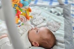 Behandla som ett barn pojken som spelar med hängande leksaker på matt framkallning royaltyfri foto