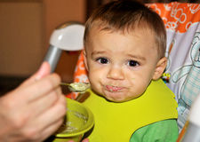 Behandla som ett barn pojken verkar till motviljar hans mat arkivfoton