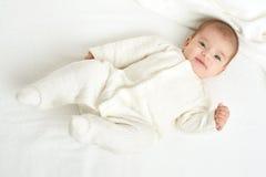 Behandla som ett barn portaitlögnen på den vita handduken i säng, tonat gult Arkivfoton