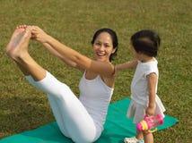 Behandla som ett barn praktiserande yoga för asiatisk kinesisk kvinna utomhus med barn gir royaltyfri foto