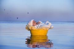 Behandla som ett barn precis i en korg simmar i vattnet arkivfoto