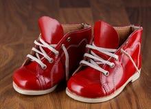 Behandla som ett barn röda skor på ett trägolv Royaltyfri Foto