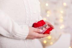 Behandla som ett barn röda sockor i moderhänder white för juldekorisolering Royaltyfria Foton
