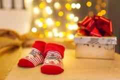 Behandla som ett barn röda sockor och julgåvor white för juldekorisolering Arkivfoton