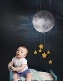 Behandla som ett barn säng Tid med stjärnor, månen och mobilen Arkivfoto