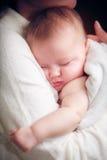 Behandla som ett barn sömn på händer av modern Arkivbild