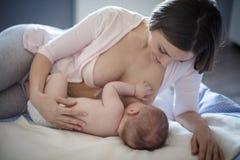 Behandla som ett barn sömnar som är lättare med hennes moder, mjölkar fotografering för bildbyråer
