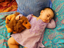 Behandla som ett barn sömnar på asiatiska tyger med leksaken Royaltyfri Bild