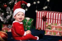 Behandla som ett barn sammanträde med gåvor under julträd royaltyfri fotografi