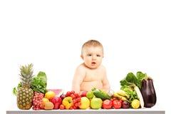 Behandla som ett barn sammanträde på en tabell mycket av olika frukter och grönsaker Fotografering för Bildbyråer