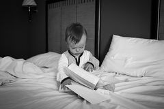 Behandla som ett barn sammanträde på sängen som bläddrar till och med en bok Royaltyfri Bild