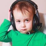 Behandla som ett barn servicetelefonoperatören i hörlurar med mikrofon (humoristiska foto) royaltyfri fotografi