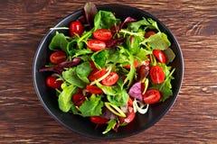 Behandla som ett barn sidasallad med körsbärsröda tomater och purjolökcirklar Royaltyfri Fotografi