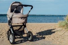 Behandla som ett barn sittvagnen på stranden Royaltyfri Foto