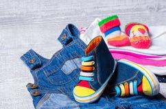 Behandla som ett barn skor för behandla som ett barn och en uppsättning av kläder Arkivbilder