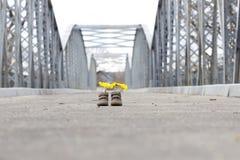 Behandla som ett barn skor med gula blommor Arkivbild