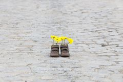 Behandla som ett barn skor med gula blommor Royaltyfri Foto