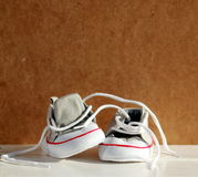 Behandla som ett barn skor med pappbakgrund Arkivfoto