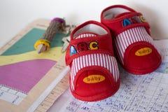 Behandla som ett barn skor på moderns dagbok. Royaltyfri Foto