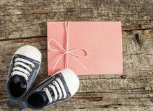 Behandla som ett barn skor på träbakgrund Arkivbild