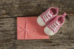 Behandla som ett barn skor på träbakgrund Arkivfoto