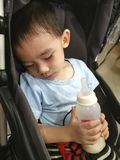 Behandla som ett barn sova innehavet mjölkar flaskan royaltyfri foto