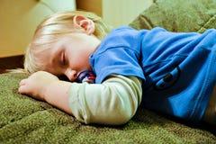 Behandla som ett barn sover på soffan Fotografering för Bildbyråer